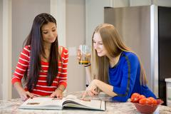 Two beautiful girls with cookbook in the kitchen, thinking what to cook for d Stock Photos