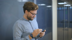A young man standing in the hallway in the office Stock Footage