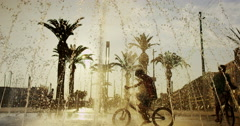 4K Young boys on bikes cooling off in fountain in the city in summertime Stock Footage