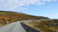 Car driving between mountains and sea full of autumn colors, from Olderfjord  Stock Footage