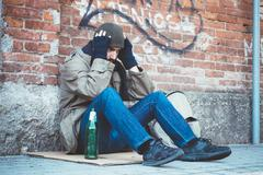 Homeless seated in the street and feeling desperate Stock Photos