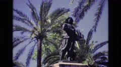 1972: a beautiful sight seeing statue in a park by a scenery of palm trees  Stock Footage