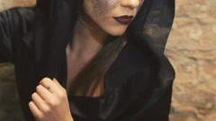 Devilish female enchantress in the black coat scaring on the camera. Slowly Stock Footage