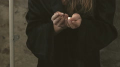 Enchantress in the coat holds dust in hands and looks on the camera. Slowly Stock Footage
