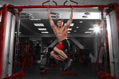 Muscular man doing pulling up on horizontal bar. Stock Photos