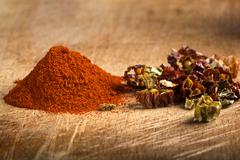 Red hot paprika powder and pieces of dried chiles Stock Photos