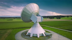 Satellite antenna dish parabolic ground station green field aerial cloudy sky Stock Footage