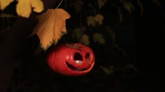 Half-turned jack-o-lantern on a chain with yellow leaves Stock Footage