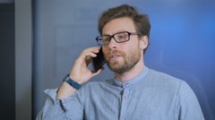 Young man talking on cell phone at modern office Stock Footage