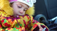 Girl sitting in a child seat in the car. Stock Footage