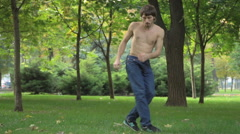 Young man dancing on a green grass Stock Footage