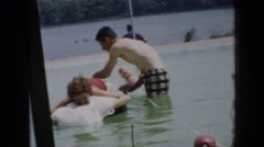 1956: the man playing with a woman in the swimming pool. CUBA Stock Footage