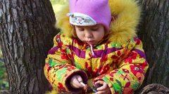 Girl in a winter jacket color eating candy. Autumn cold. Stock Footage