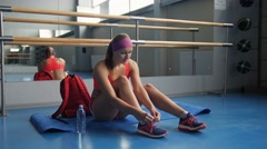 Beautiful woman tying shoelaces at gym Stock Footage
