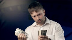 Concentrated young man counts a certain amount of money for someone Stock Footage
