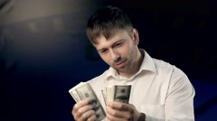Young man counting some money attentively then gazes at camera Stock Footage