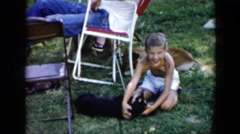 1956: girl on grass playing with holding puppy near person rocking in red chair Stock Footage