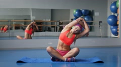 Beautiful young woman stretching the muscles of her arms and back Stock Footage