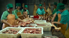 Manufacture. Butchering Room. Workers in Green Uniform Cutting Meat Off the Stock Footage