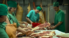 Butchering Room. Heaps of Pork on the Table. Workers in Green Uniform Taking Stock Footage