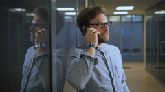 Blonde man in a business center talking on his black smartphone Stock Footage