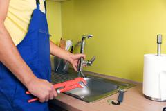 Plumber working in domestic kitchen, repairing faucet Stock Photos