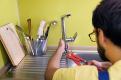 Plumber installing, repairing water tap in kitchen Stock Photos