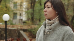 Young sadly girl in a gray coat waiting for the meeting in the autumn park Stock Footage