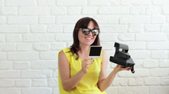 Young smiling woman in sunglasses browses instant camera photo frames  HD Stock Footage