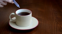 Female hand poisoning tea with syringe Stock Footage