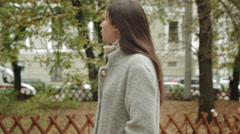 Young girl in a gray coat waiting for the meeting in the autumn park Stock Footage