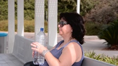 Woman drinks water in bright sunny day Stock Footage