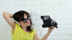 Young happy woman in sunglasses taking selfie with instant camera  HD Stock Footage