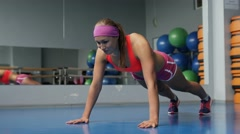 Gorgeous blonde woman warming up and doing some push ups a the gym Stock Footage