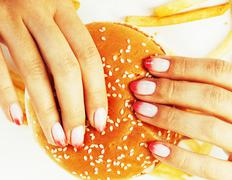 Woman hands with manicure holding hamburger and french fries iso Stock Photos