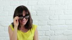 Young smiling woman with sunglasses blinking and blowing kiss HD Stock Footage