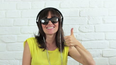 Stylish young woman with headphones making thumbs up gesture HD Stock Footage