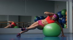 Beautiful young girl doing exercises with fit ball at sport gym Stock Footage