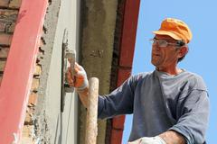 Builder Worker At Plastering Facade Work Stock Photos