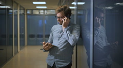 Blonde man in office building talking on the phone and simultaneously scans news Stock Footage