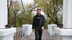 Handsome bearded man in black leather jackets in the park Stock Footage