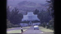 1961: car moves towards white large bungalow midst of greenery and mountain Stock Footage