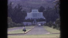 1961: woman with bags waiting on a curb in front of stately white building Stock Footage