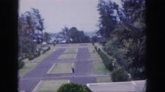 1961: plaza with plots bordered by street, plantings and building Stock Footage