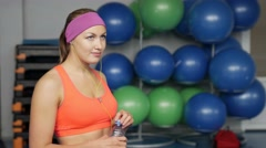Beautiful fitness athlete woman resting drinking water after work out exercising Stock Footage