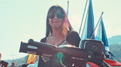 Pan from motorcycle wheel to biker lady with sunglasses Stock Footage