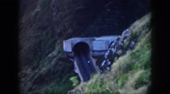 1961: a car exiting from a tunnel opening on the side of a mountain HAWAII Stock Footage