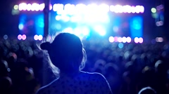 Young girl having fun dancing at a rock concert on the background of the scene Stock Footage