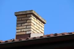 Roof detail of a detached house with red roof tile and beige chimney against  Stock Photos