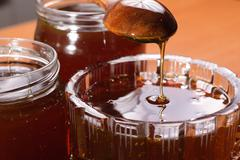 Honey dripping from wooden spoon Stock Photos